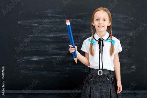 Plakat Mała dziewczynka z ołówkiem przeciw blackboard. Koncepcja szkoły