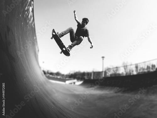 Valokuvatapetti Skateboarder doing ollie on ramp -  black and white