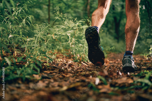 Fotografía  Muscular calves of a fit male jogger training for cross country forest trail race in nature park