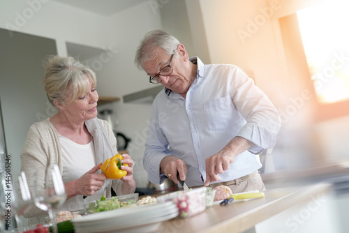 Poster Cuisine Senior couple cooking together in home kitchen