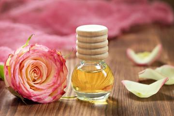 Obraz na płótnie Canvas Rose essential oil in glass bottle on wooden background