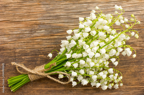 Wall Murals Lily of the valley Vintage bouquet of wild flowers, the white scented lilies of the valley on an old wooden plank closeup