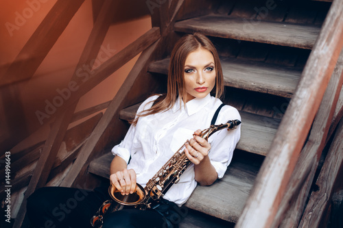 Obraz na plátně  Young attractive girl sitting on steps in white shirt with a saxophone - outdoor in old town