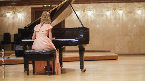 Cute teenager girl plays piano in the concert hall at scene Fotobehang