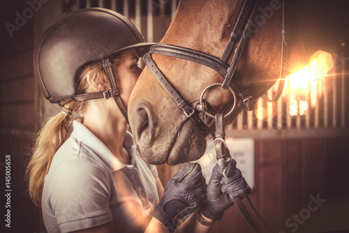 Young women kissing her horse in barn