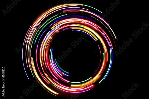 Foto  Abstrakte drehende Neonlichter masern mit schwarzem leerem Kopienraum nach innen
