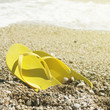 Pair of yellow flip flops on a beach