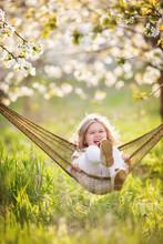Pretty Child Girl In Hammock In Blossom Garden