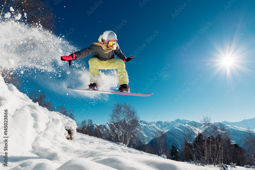 Fotografía Girl is jumping with snowboard