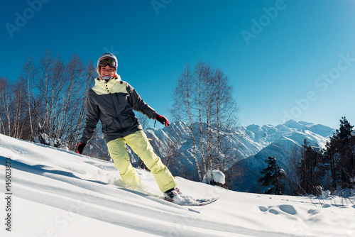 Fotomural girl is riding on snowboard and smiling
