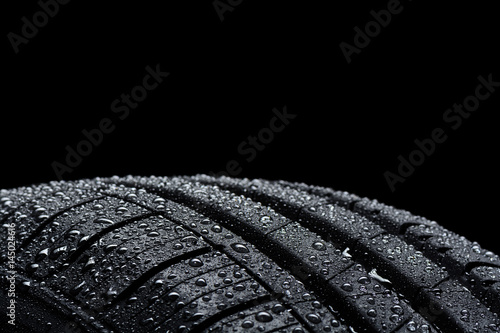 Fotografie, Obraz Car tire covered with water drops on black background