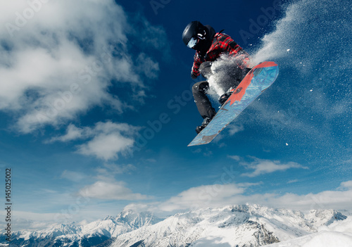 obraz dibond snowboarder is jumping with snowboard from snowhill