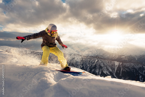 Fotografía snowboarder is riding on the sunset