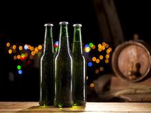 Glass Bottles Of Beer And Wooden Barrel On Bar Lights Background