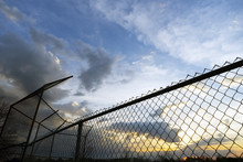 Empty Community Baseball Diamond And Fence In Silhouette Against A Sunset Sky At Dusk