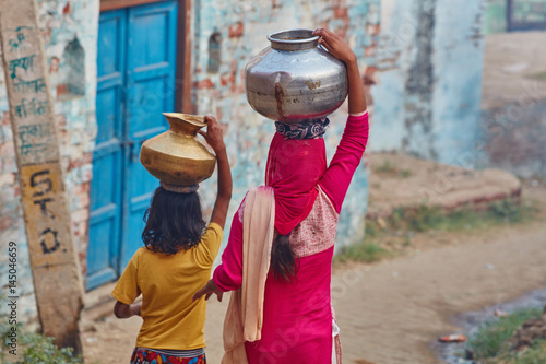 Photo  Vrindavan, 22 October 2016: Two women carrying jars on their head, in Vrindavan,