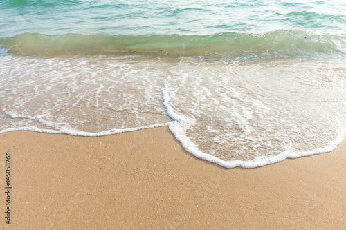 Soft wave of blue ocean on sandy beach at sunny day. Background subject is soft focus