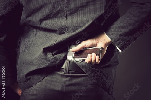 Photo  Gun concealed, A man, policeman or gangster concealing his gun behind his back
