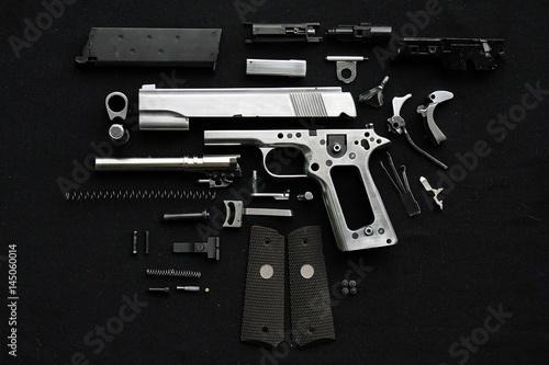 Fotomural  Disassembled handgun on black background,