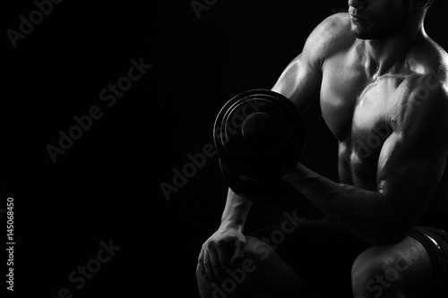 Valokuvatapetti Low key light monochrome cropped close up of a shirtless ripped athletic man exercising with dumbbells flexing his bicep muscles copyspace lifestyle fitness gym sport motivation athletics activity