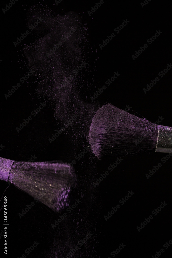 Plakát  Make up brush with purple dust on black background
