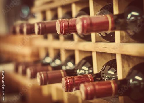 Leinwand Poster Red wine bottles stacked on wooden racks