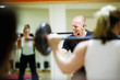 Cheerful instructor lifting barbell in class at gym