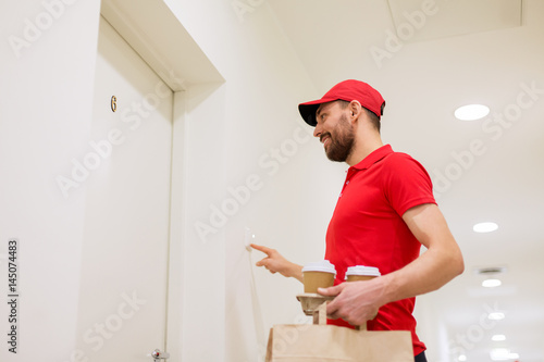 фотографія  delivery man with coffee and food ringing doorbell