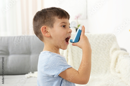 Obraz na plátně Little boy using asthma inhaler at home