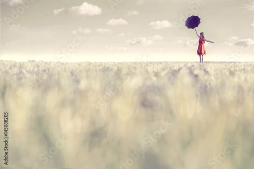 Fotografie, Obraz  Surreal woman dressed in red walks with her umbrella in the middle of nature
