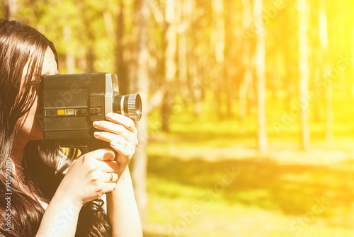 Fotografie, Obraz  Woman with vintage video camera outdoor