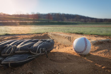 Baseball Glove And Baseball On Pitcher's Mound With Sun Rising In Background