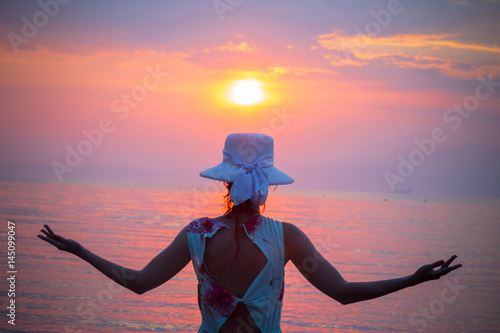 Back view of female enjoying the sunset over sea Poster