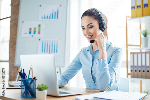 Valokuvatapetti Portrait of young smiling happy woman in headphones working as operator of call