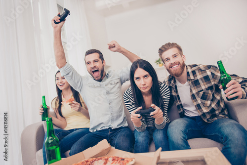 Young people having home party with video games, pizza and beer Wallpaper Mural