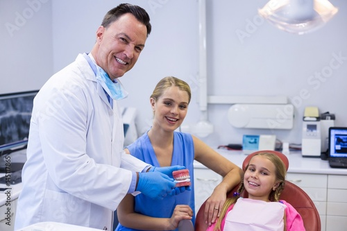 Canvas Prints Akt Dentist showing young patient how to brush teeth