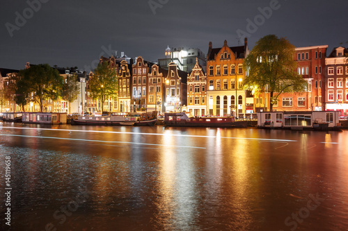 Canvas Prints Countryside Amsterdam canal Amstel with typical dutch houses, houseboat and luminous track from the boat at night, Holland, Netherlands.