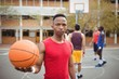 Male basketball player holding basketball in basketball court