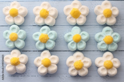 Canvas Print White, blue and yellow daisy marshmallow sweets on duck egg blue painted table