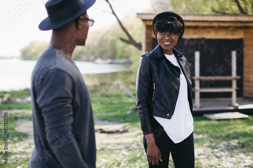 Poster Equitation A beautiful and stylish young african couple in sunglasses and hats walking on a outdoor of summer.
