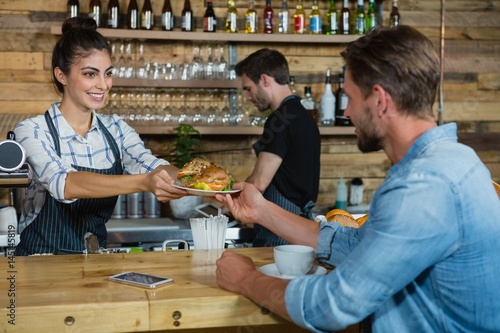 Fotografía  Waitress serving breakfast to man at counter