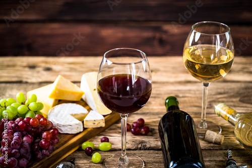 Leinwand Poster Wine bottles with grapes and cheese  on wooden rustic background