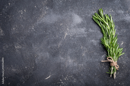 Rosemary on concrete table. Herbs and spices. Cooking ingredients. Top view and copy space for your recipe