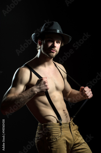 5df1fab6ab3 Suspenders and hat on naked male body. Attractive handsome sexy man played  with suspenders. Cowboy on black background