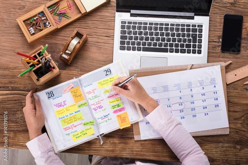 Cuadros en Lienzo  Businesswoman Writing Schedule In Calendar Diary