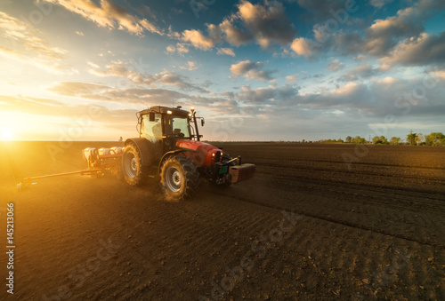 Photo  Farmer with tractor seeding - sowing crops at agricultural field in spring
