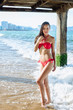 Brunette woman standing near pier column. Beautiful young attractive girl in red bikini looking at the sea.