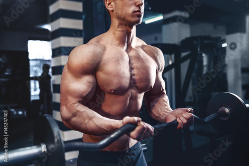 Valokuva  Muscular bodybuilder guy doing exercises on biceps with big dumbbell in gym