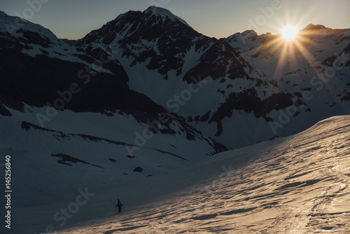 Snowboarder going up mountain in sunrise light
