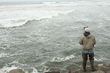 Man Surf Fishing On The Jetty.